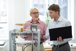An older employee teaching his younger colleague how to use a 3D printer. Source: iStock.